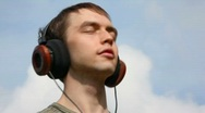 Young men listen music in headphone on sky background Stock Footage
