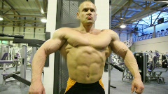 Bodybuilder straining muscles in gym Stock Footage