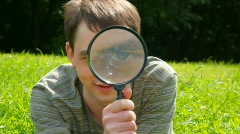 Young men looks through a magnifying glass, looking to camera Stock Footage