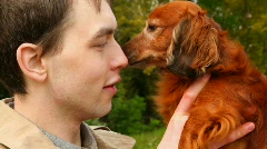 Dog licking men's nose Stock Footage