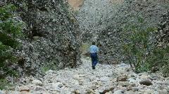 Man walks box canyon away 2 P HD 3516 Stock Footage