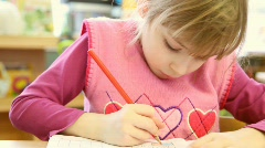 Girl sitting in classroom, she takes blue soft-tip pen and start to draw - stock footage