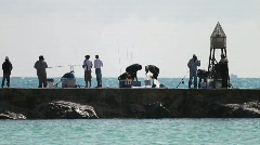 Fishermen Fishing off a Jetty in rough seas Stock Footage
