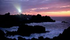 Lighthouse on wild coastline at dusk Stock Footage