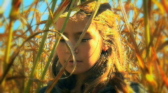 Girl looking at cornstalks on beautiful autumn day Stock Footage
