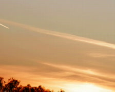 Vapour trail from plane at sunset Stock Footage