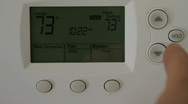 Stock Video Footage of Adjusting a Thermostat