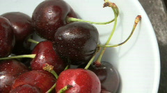 CU BOWL OF CHERRY'S ON GARDEN TABLE Stock Footage