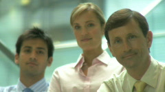 MS GROUP PORTRAIT 2 MALE AND ONE FEMALE IN OFFICE BUILDING  SHIFT OF FOCUS Stock Footage