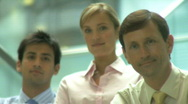 Stock Video Footage of MS GROUP PORTRAIT 2 MALE AND ONE FEMALE IN OFFICE BUILDING  SHIFT OF FOCUS