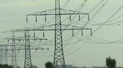 Zoom out on electricity pylon and powercables at sunset Stock Footage