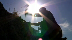 Silhouetted Man Hitting Rocks Outside in the Desert Stock Footage