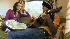 Boy playing guitar for female Stock Footage