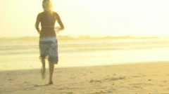 WS FOCUS SHIFT REAR VIEW OF A YOUNG WOMAN RUNNING TO THE SEA Stock Footage