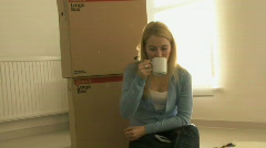 WS OF A YOUNG WOMAN TAKING A BREAK FROM MOVING HOUSE Stock Footage