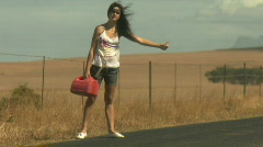 LS OF A YOUNG WOMAN HITCHHIKING Stock Footage