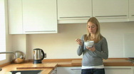 MS PAN OF A YOUNG WOMAN EATING A YOGHURT Stock Footage