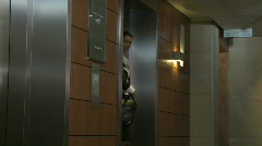 LS PAN OF A BUSINESSWOMAN WALKING OUT OF A LIFT Stock Footage