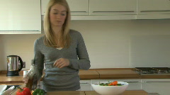 CU PAN OF A YOUNG WOMAN POURING SALAD DRESSING ONTO A SALAD Stock Footage