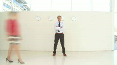 WS PAN OF A BUSINESSMAN STANDING STILL WITH BLURRED PEOPLE WALKING PAST Stock Footage