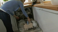 WS OF A YOUNG WOMAN CLOSING DISHWASHER DOOR Stock Footage