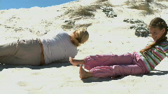 MS OF A GRANDMOTHER AND GRANDDAUGHTER ROLLING DOWN A SAND DUNE Stock Footage
