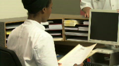 MS PAN OF A RECEPTIONIST HANDING OVER A FILE TO A DOCTOR Stock Footage