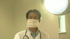 MS PAN ZI OF A DOCTOR REMOVING A SURGICAL MASK Stock Footage