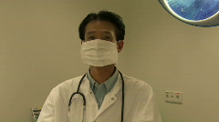 MS PAN OF A DOCTOR REMOVING A SURGICAL MASK Stock Footage