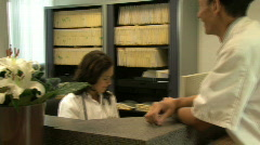 MS PAN OF A DOCTOR HANDING OVER A FILE Stock Footage