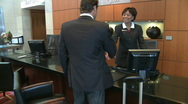Stock Video Footage of MS PAN OF A BUSINESSMAN CHECKING IN AT A RECEPTION DESK