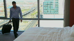 LS PAN OF A BUSINESSMAN WALKING INTO HIS HOTEL ROOM AND LYING ON THE BED Stock Footage