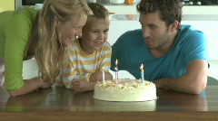 MS OF A BOY BLOWING OUT CANDLES ON A BIRTHDAY CAKE Stock Footage