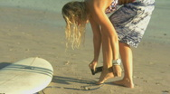 MS OF A YOUNG WOMAN TYING A SURFBOARD LEASH TO HER ANKLE AND THEN WALKING OFF WI Stock Footage