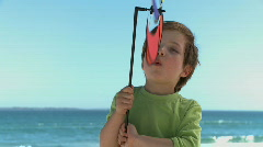 MS OF A BOY BLOWING ON A PIN WHEEL Stock Footage