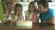 MS OF A GIRL BLOWING OUT CANDLES ON A BIRTHDAY CAKE Stock Footage