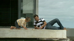 LS OF A FATHER AND SON PLAYING WITH A TOY BOAT - stock footage