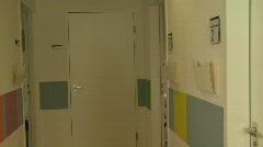 LS OF DOCTORS WALKING DOWN A CORRIDOR READING A FILE AND ENTERING A ROOM - stock footage