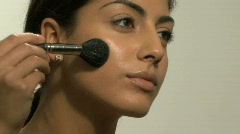 CU OF A YOUNG WOMAN APPLYING BLUSHER - stock footage