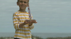 MS PAN OF A BOY HOLDING A TOY BOAT Stock Footage