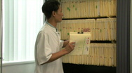 MS PAN ZI OF A DOCTOR AT A FILING CABINET Stock Footage