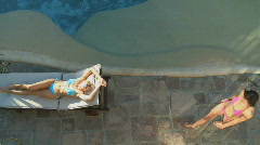 WS PAN OF A WOMAN WALKING PAST A WOMAN SUNBATHING ON A SUN LOUNGER Stock Footage
