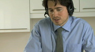 CU ZO OF A BUSINESS MAN USING A HEADSET AND LAPTOP Stock Footage
