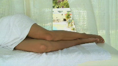 MS PAN OF A YOUNG WOMAN LYING ON A MASSAGE TABLE IN SPA Stock Footage