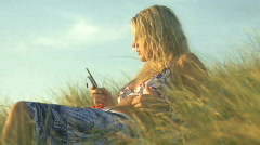 MS OF A YOUNG WOMAN SUNBATHING AND USING A CELL PHONE Stock Footage