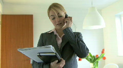WS OF A FEMALE ESTATE AGENT TALKING ON CELL PHONE - stock footage