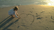 LS OF A GIRL DRAWING A HEART IN THE SAND Stock Footage