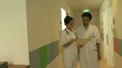 MS ZI OF DOCTORS READING A FILE Stock Footage
