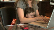 MS PAN OF A MOTHER USING A LAPTOP AND HOLDING HER BABY Stock Footage