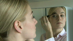 WS ZO OF A YOUNG WOMAN APPLYING MASCARA Stock Footage